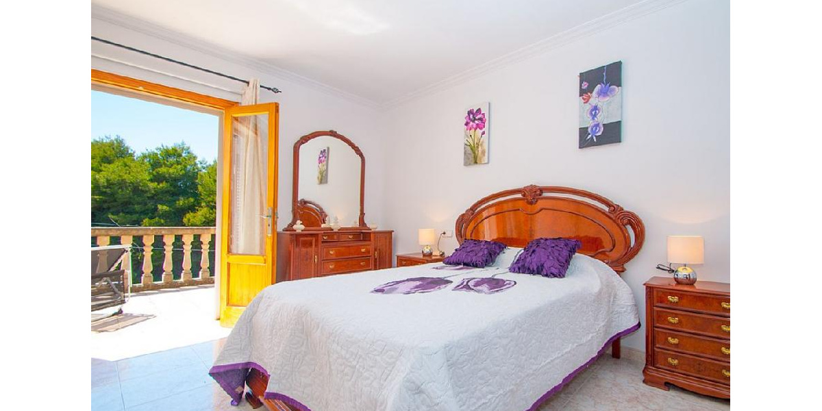 Double purple bedroom with stylish furniture also has a terrace and bathroom..