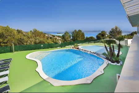 Fabulous swimming pool with adults and children, hammocks line and sea views